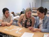 Tres alumnes del nivell elemental fent una partida de dòmino fonètic
